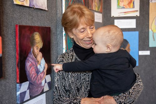 An older adult smiles at a baby they are holding. The baby is pointing at a painting on the wall, which is of the same older adult holding the same baby.
