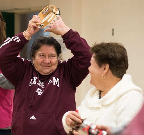 An older adult in a maroon-colored sweatshirt holds a tambourine above their head and smiles at another older adult, who is smiling back at them and facing away from the camera.
